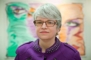 Portraitfoto lächelnder Anja Winter. Sie hat kurzes graues Haar und trägt eine kupferfarbene Brille, dazu einen lilafarbenen Blazer mit paillettenbesticktem Stehkragen