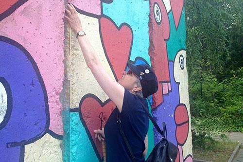 Anja Winter tastet Teilstück der Berliner Mauer, Foto