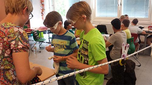 Schüler mit Simulationsbrillen beim Wäscheaufhängen