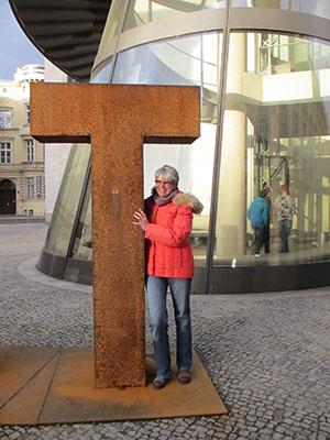 Foto von Anja Winter, die sich lachend gegen die überlebensgroße tastkunst Initiale aus oxidiertem Stahl lehnt. Sie trägt eine rote Daunenjacke und blaue Jeans
